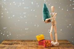 Figura artística de madeira que guarda a árvore e as caixas de presente de Natal Conceito do feriado do Natal Imagens de Stock Royalty Free