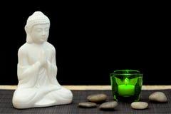 Figura bianca nella posa di meditazione con i ciottoli e la candela Immagini Stock Libere da Diritti