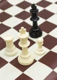 Figura blanca rey negro desafiador del ajedrez Imagenes de archivo