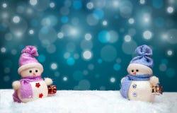 Figura bonecas dos bonecos de neve com os flocos de neve no fundo Fotografia de Stock