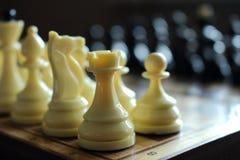 Figura branca da xadrez contra peças do jogo de xadrez brancas e pretas unfocused no tabuleiro de xadrez de madeira como o concei Imagem de Stock Royalty Free