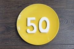 Figura cinquanta per il piatto giallo Fotografia Stock Libera da Diritti