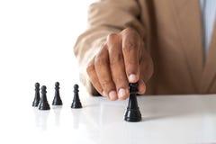 Figura commovente di scacchi dell'uomo di affari con il gruppo dietro - strategia o Fotografie Stock