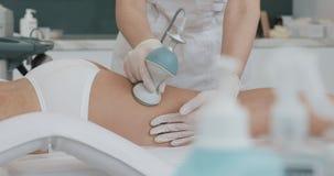 Figura correzione dell'hardware Cosmetologia a macchina Bella donna che ha cavitazione, procedura che rimuove le celluliti lei fotografia stock