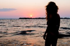 Figura da mulher no roupa de banho que olha o nascer do sol de surpresa perto do mar na praia imagem de stock royalty free