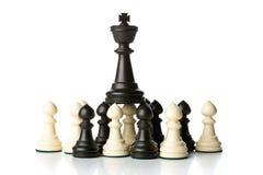 Figura da xadrez do rei sobre figuras da xadrez do penhor Foto de Stock
