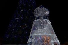 Figura de la nieve virginal y cortada del hielo cerca del árbol de navidad imagenes de archivo