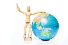 Figura de madeira isolada com o globo no fundo branco fotografia de stock