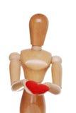 Figura de madeira que prende as mãos vermelhas do foco do coração Fotografia de Stock Royalty Free