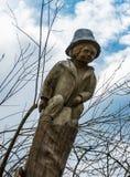 Figura de madeira, velha dos meninos em um tronco da árvore fotos de stock royalty free