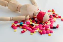 Figura de madera ciega con las píldoras en el piso blanco Foto de archivo libre de regalías