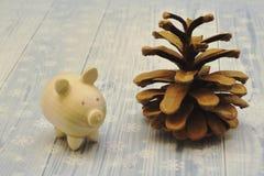 Figura de madera del cochinillo y del cono hermoso grande del pino en el fondo ligero adornado con los copos de nieve fotos de archivo libres de regalías
