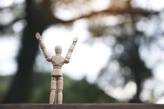 Figura de madera modelo de las manos de levantamiento y de la situación de un hombre en la tabla de madera con el fondo de la fal foto de archivo