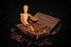 Figura de madera que se sienta en una caja de madera con el dinero Foto de archivo