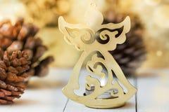 Figura de oro del ángel de la Navidad, conos del pino, fondo luminoso chispeante, festivo, plantilla de la tarjeta de felicitació Fotografía de archivo