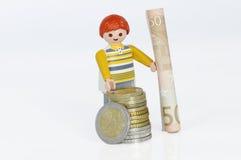 Figura de Playmobil con el dinero Imagenes de archivo