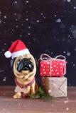 Figura de um cão em um chapéu do Natal em uma tabela de madeira Símbolo do ano seguinte Fotografia de Stock Royalty Free