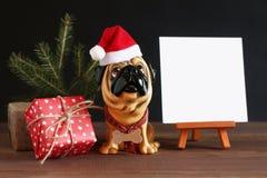Figura de um cão em um chapéu do Natal em uma tabela de madeira Símbolo do ano seguinte Imagens de Stock