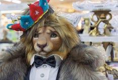 A figura de um leão é vestida em um casaco de pele, em um revestimento de cauda com uma borboleta e em uma coroa em sua cabeça foto de stock