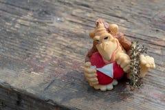 Figura de um macaco com um coração em um fundo de madeira Fim acima Macro fotografia de stock royalty free