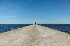 Figura de un hombre que camina en un embarcadero en Nida, Lituania foto de archivo libre de regalías