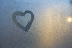 Figura del corazón en una ventana congelada en la ciudad imagen de archivo