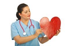 Figura del cuore della holding della donna del medico fotografie stock libere da diritti