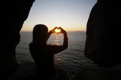 Figura del cuore fatta con le mani della ragazza Fotografie Stock