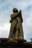Figura del monje de rogación en la puerta que lleva al cementerio, Fotografía de archivo