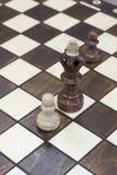 Figura della parte di scacchi che si leva in piedi sulla scheda di scacchi Immagini Stock Libere da Diritti