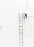 Figura di lavoro che scala una parete Fotografia Stock Libera da Diritti