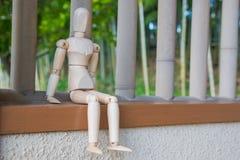 Figura di legno che si siede sulla finestra dell'architrave Fotografia Stock Libera da Diritti