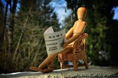 Figura di legno che si siede sulla sedia del patio e che legge giornale Immagini Stock Libere da Diritti
