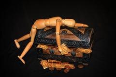 Figura di legno che si trova su una scatola di legno con soldi dentro Immagini Stock Libere da Diritti