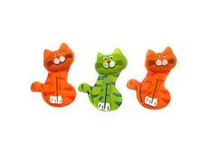 Figura di legno del gatto tre dipinta brillantemente in arancia e nel verde Fotografie Stock