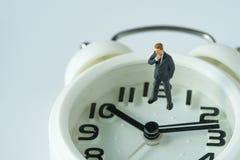 Figura di pensiero miniatura dell'uomo d'affari che sta sul Cl bianco dell'allarme Immagine Stock Libera da Diritti