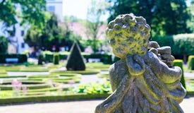 Figura di pietra di un angelo barrocco davanti ad un fondo deliberatamente vago con un giardino barrocco fotografia stock