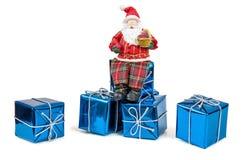 Figura di Santa Claus che si siede sui contenitori di regalo Fotografie Stock