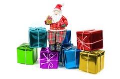 Figura di Santa Claus che si siede sui contenitori di regalo variopinti Immagini Stock Libere da Diritti