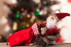 Figura di Santa con una borsa dei regali sul boke Immagine Stock