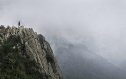 Figura di un uomo sulla cima della montagna Fotografie Stock