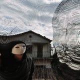 Figura diabolica mascherata dietro la finestra filettata Immagini Stock