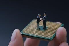 Figura diminuta aperto de mão dos povos dos homens de negócios no chip de computador imagens de stock royalty free