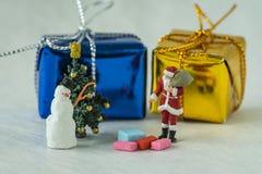 Figura diminuta Papai Noel que está com as caixas de presente atuais Foto de Stock Royalty Free