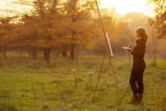 Figura do artista da jovem mulher que pinta uma imagem na armação, menina que aprecia a natureza do outono e o trabalho inspirado fotos de stock