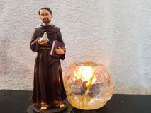 Figura do brinquedo de St Francis que guarda um pássaro branco da pomba e uma Bíblia ao lado de uma vela ardente imagem de stock