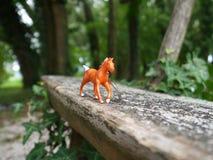 Figura do cavalo no banco de madeira no parque Imagem de Stock Royalty Free