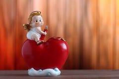 Figura do cupido no coração vermelho grande Fotografia de Stock