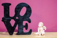 figura do cupido perto do amor da palavra fotografia de stock