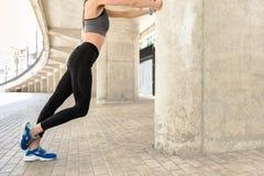 Figura esile di scaldarsi dell'atleta femminile Fotografia Stock
